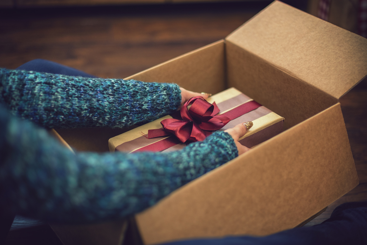 woman opening a package with a gift inside