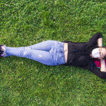 woman lying in grass enjoying the outdoors