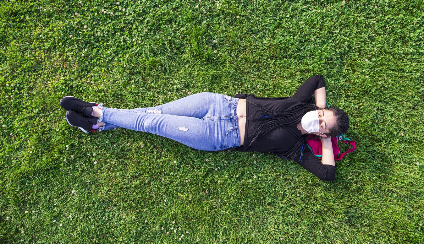 woman lying in grass enjoying the outdoors