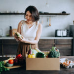 woman in kitchen unpacking groceries from specialty food store
