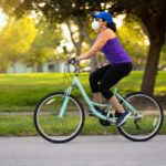 woman biking in park | bike stores in Louisville